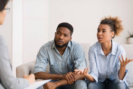 Moglie afroamericana che parla con consigliere seduto sul divano accanto al marito.