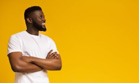 Young pensive african man looking upwards at empty space on yellow studio