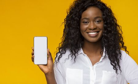 Awesome new phone. Pretty african american woman showing brand new smartphone with blank screen Фото со стока