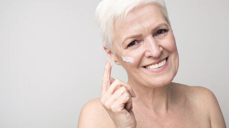 Morning routine. Aged woman applying face cream on cheek, light panorama with free space Banque d'images