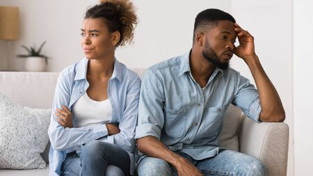 Not on speaking terms. Frustrated afro couple looking away avoiding eye contact sitting on couch.