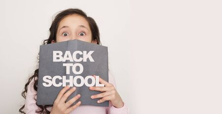 Back to school concept. Girl peeking out of the book with title on white with copy space