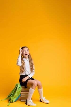 Idea Or Question. Adorable Schoolgirl Sitting On Stack Of Books Pointing Finger Up On Yellow Studio