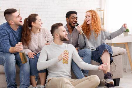 Amis heureux chantant du karaoké, s'amusant et passant du temps ensemble à la maison