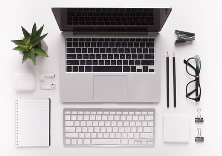 Business concept. Top view of white office desk with laptop and other supplies