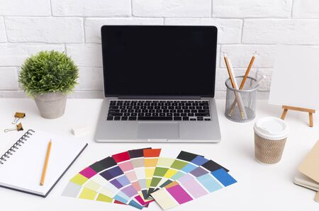 Designer workplace with laptop, cup of coffee and office supplies on white table, blank screen