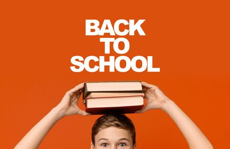 Back to school. Positive schoolboy holding stack of books on his head, orange studio background