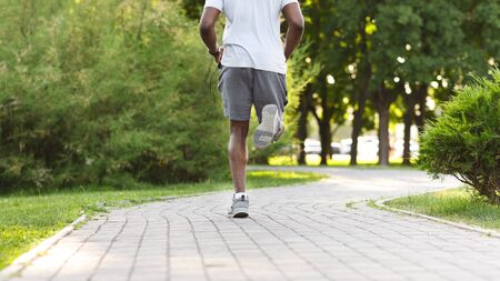 Fit Body Concept. Body Of Black Atlete Running Along The Park Path, free space