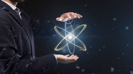 Man holding glowing atom hologram. Concept of scientific research and modern technology, panorama