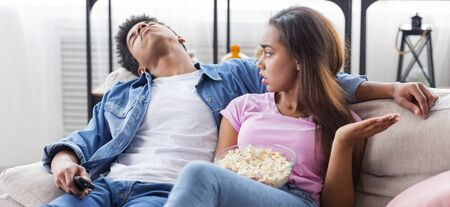 Incompatibility problems. Guy fell asleep during watching boring movie at home, his girlfriend is angry, panorama