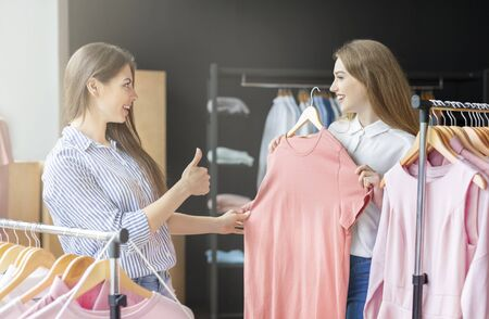 I like it. Elegant Caucasian Woman Showing Thumb Up To Her Friend As She Likes Chosen Dress, shop interior