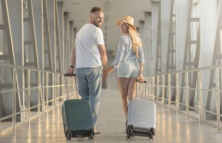 Travelling concept. Happy couple walking with suitcases at airport terminal, waiting for departure