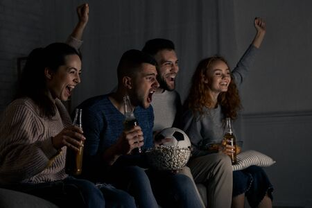 Happy football fans cheering for favourite team, watching match at home in dark room Zdjęcie Seryjne