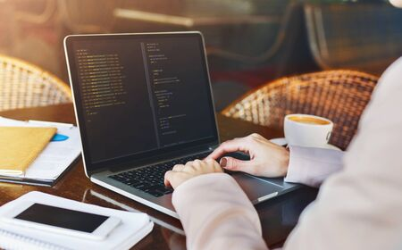 Young woman programmer writing code on laptop in cafe and drinking morning coffee, background 写真素材