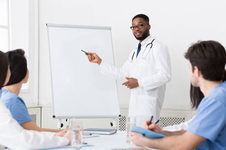 African-american cardiologist giving lecture for interns using pictures on whiteboard