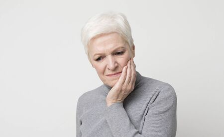 Teeth problem. Elderly woman suffering from strong tooth pain, panorama with copy space