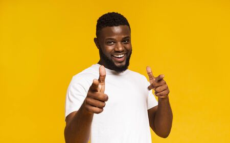 Flirty black man pointing at camera with both hands, yellow studio background