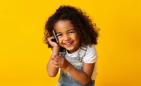 Cute afro girl talking on cellphone and smiling on yellow studio background Stock Photo