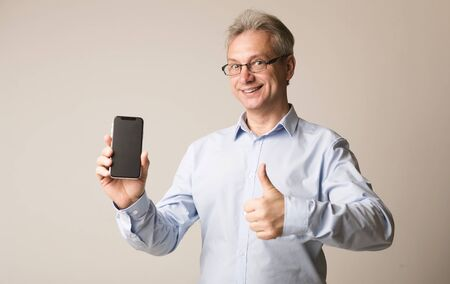 Senior man showing blank screen and showing thumb up over gray background Imagens