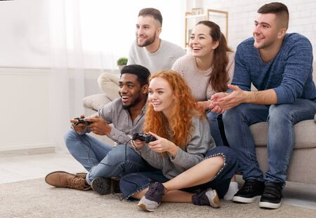 Diverse friends playing video games, having fun and sitting on floor at home