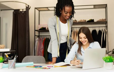 Two Young Diverse Dressmakers Designing New Fashionable Clothing Line In Their Showroom. Copy Space Stock Photo