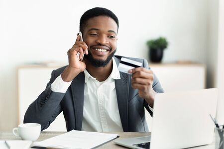 Easy payments. Happy african worker holding credit card after online purchase and talking on mobile phone with customer service.