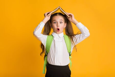 De vuelta a la escuela. Chica estudiante de escuela primaria conmocionada que cubre la cabeza con el libro sobre fondo amarillo. Foto de estudio, espacio de copia Foto de archivo