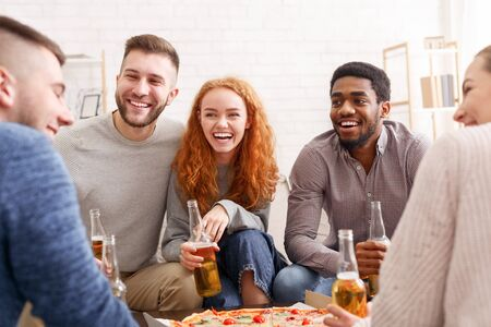 Celebrate meeting. Happy friends talking, eating pizza and drinking beer at home Stockfoto - 128617039