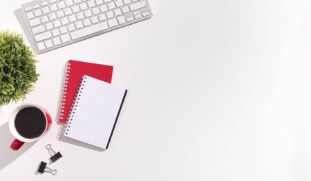 Work creative. Red and white notebooks and keyboard on white office table with copy space
