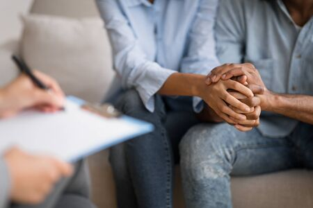 Couples Therapy Concept. Unrecognizable Black Man And Woman Holding Hands At Marital Psychologist's Office. Cropped, Selective Focus Stockfoto - 128617719