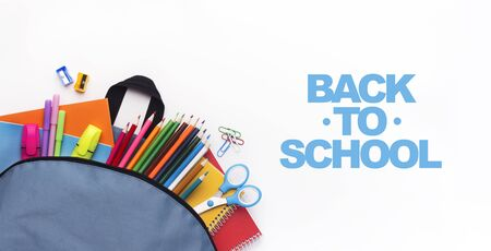 School backpack with colored stationery on white background with free space