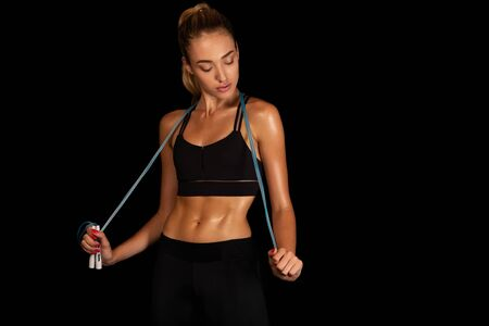 Fitness Lifestyle. Woman Holding Jump Rope Over Black Background In Studio. Copy Space Stock Photo