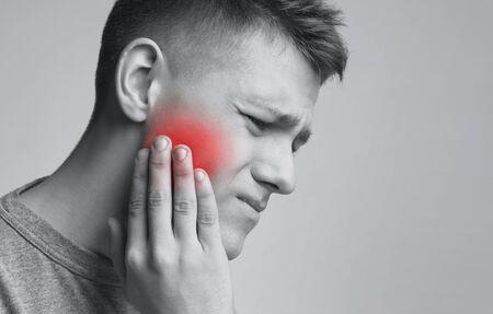 Problema dentale. Giovane che soffre di forte mal di denti, foto monocromatica con zona infiammata rossa, spazio libero