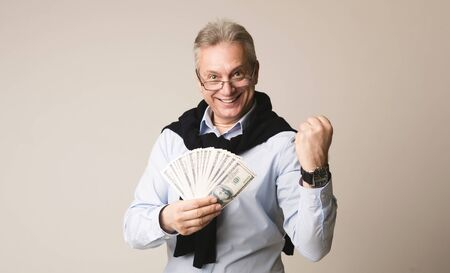Happy senior businessman holding money over gray background Imagens