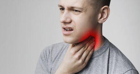 Junger Mann, der an Mandelentzündung leidet, seinen Hals einschlägt, Panorama, freier Raum