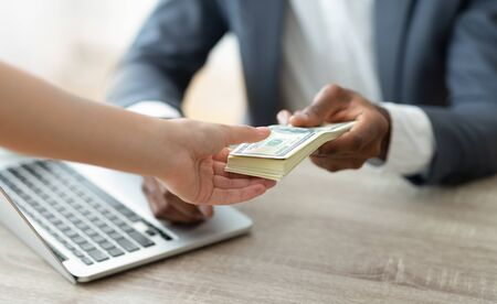 Close-up of unrecognizable black bank manager holding stack of dollars giving credit to customer. Copy space