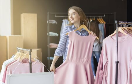 I want to wear this elegant dress. Dreamy caucasian girl trying on pink dress at clothing store, copy space