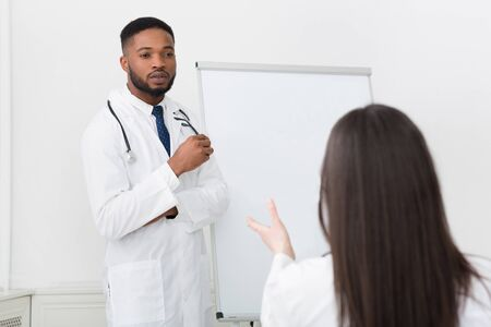 Medical lecture. Active intern asking question to practitioner at seminar