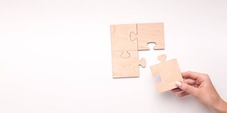 Woman creating wooden puzzle of four pieces with copy space for text on white background, panorama
