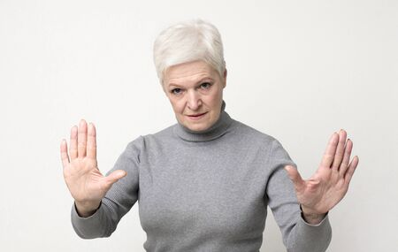 Senior female practicing hypnosis, looking mysteriously at camera, panorama