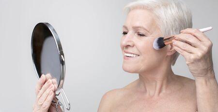Portrait of beautiful senior woman doing makeup, applying blush to her cheek, panorama