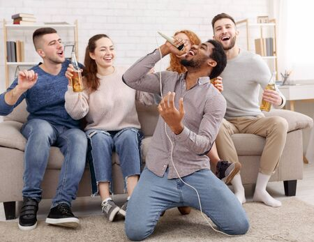 Karaoke party concept. Happy friends singing at home, having fun together