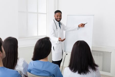 African-american cardiologist giving information to interns at medical seminar in hospital
