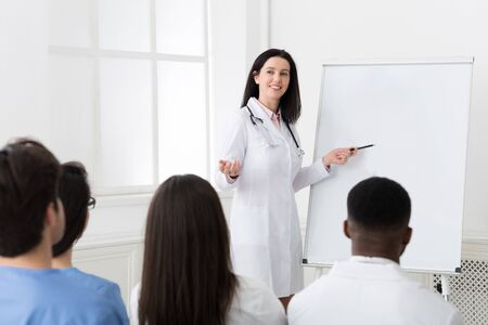 Successful doctor sharing experience with colleagues at medical consultation in hospital Stock Photo