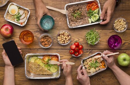 Family Lunch in delivery foil boxes with healthy food on wooden background, cellphone with blank screen for advertisement
