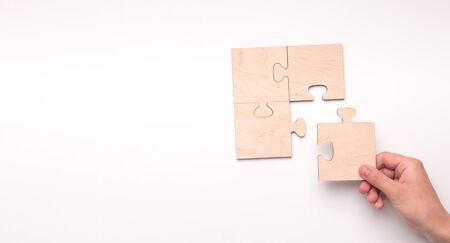 Woman creating picture with missing piece of wooden puzzle on white panorama background with copy space