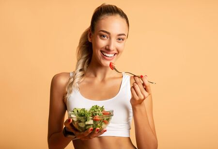 Healthy Diet. Smiling Woman Eating Salad Over Pink Studio Background. Free Space For Text Stock Photo