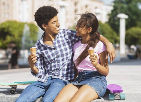Youth concept. Playful african american teenage couple eating ice cream on a date outdoors Stock Photo
