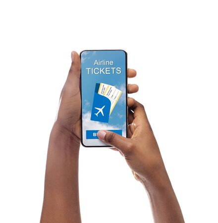 Airline tickets application. Closeup of black ladys hands holding cellphone with opened app for buying flights. Isolated, copy space. Banco de Imagens