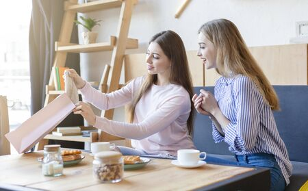 Caucasian Girl Showing Purchases Her Girlfriend At Cafe, drinking coffe and eating waffles, copy space